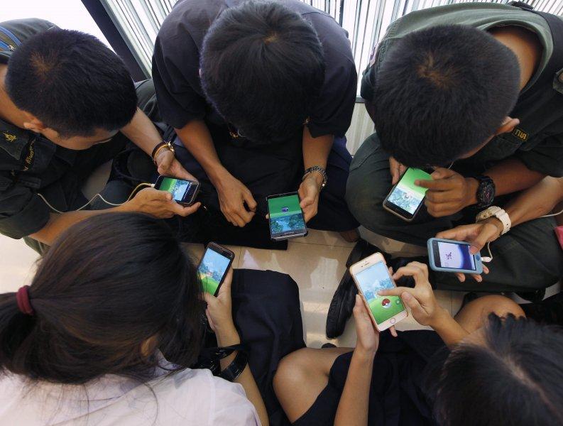 """TAILANDIA POKEMON GO:POK04 BANGKOK (TAILANDIA) 08/08/2016.- Estudiantes tailandeses juegan al videojuego """"Pokemon Go"""" desde su teléfono móvil en un centro comercial en Bangkok, Tailandia, hoy, 8 de agosto de 2016. El videojuego permite a los usuarios utilizar el GPS para buscar personajes en cualquier entorno. La Comisión Nacional de Radiodifusión y Telecomunicaciones (NBTC) está a la espera de que se emitan restricciones en zonas contra el videojuego, especialmente en emplazamientos religiosos o monumentos históricos como el Palacio Royal o los templos budistas, así como en hospitales y áreas privadas. La NBTC también expresó su preocupación por los usuarios, ya que podrían incrementar de forma peligrosa las facturas de telefonía móvil y podrían sufrir accidentes por distracciones. EFE/Rungroj Yongrit"""